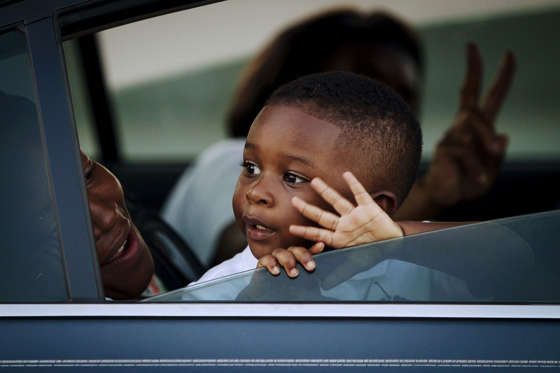 A boy waves to people gathered on the Arthur Ravenel Jr. bridge in Charleston, June 21, 2015, after the first service at the Emanuel African Methodist Episcopal Church since a mass shooting left nine people dead. Hundreds of people packed the sweltering Emanuel African Methodist Episcopal Church in Charleston for an emotional memorial service on Sunday just days after a gunman, identified by authorities as Dylann Roof, a 21-year-old white man, shot dead nine black church members.   REUTERS/Carlo Allegri