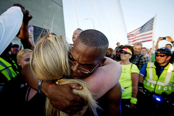 People hug as they gather on the Arthur Ravenel Jr. bridge in Charleston, June 21, 2015, after the first service at the Emanuel African Methodist Episcopal Church since a mass shooting left nine people dead. Hundreds of people packed the sweltering Emanuel African Methodist Episcopal Church in Charleston for an emotional memorial service on Sunday just days after a gunman, identified by authorities as Dylann Roof, a 21-year-old white man, shot dead nine black church members.   REUTERS/Carlo Allegri