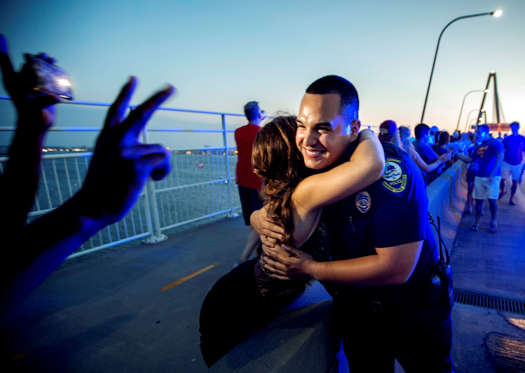 Mt. Pleasant Police Officer Brandon Montano gets high-fives and hugs as thousands of people march across of Charleston's main bridge in a show of unity after nine black church parishioners were gunned down during a Bible study, Sunday, June 21, 2015, in Charleston, S.C. (AP Photo/Stephen B. Morton)