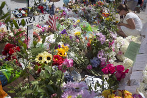 A woman kneels at a makeshift memorial for victims of a mass shooting, outside t...