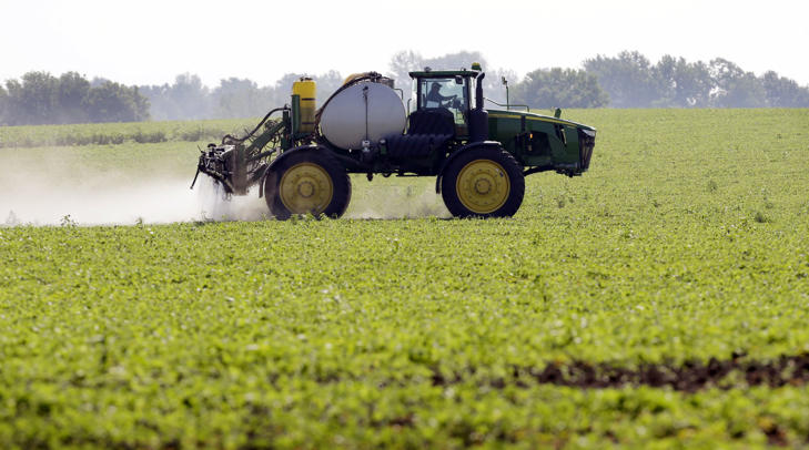 This July 11, 2013, file photo shows Blake Beckett of West Central Cooperative as he sprays a soybean field, in Granger, Iowa.