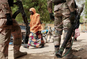A woman walks past Nigerian Soldiers at a checkpoint in Gwoza, Nigeria, a town newly liberated from Boko Haram.