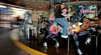 Danielle Rotiroti and her daughter Julia Rotiroti, 2, ride the carrousel together at Hersheypark in  Hershey, Pa.