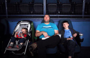 Everett Hughes, 1, watches the movie Cinderella alongside his dad, Iraq War veteran Jonah Hughes and brother, Koen Hughes, 10, at a movie theater in Hartford, CT, on March 27, 2015. Jonah has suffered from PTSD, as well as a brain injury and a spinal injury, after returning home.