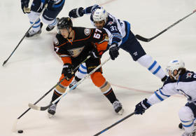 Anaheim Ducks center Rickard Rakell (67) keeps the puck from Winnipeg Jets defenseman Dustin Byfuglien (33) in the first period of game two of the first round of the the 2015 Stanley Cup Playoffs at Honda Center.