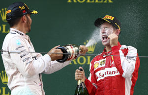 Lewis Hamilton of Great Britain and Mercedes GP celebrates on the podium with Sebastian Vettel of Germany and Ferrari after winning the Formula One Grand Prix of China.