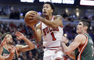 Chicago Bulls guard Derrick Rose, center, drives to the basket against Milwaukee Bucks forward Ersan Ilyasova, right, and guard Michael Carter-Williams during the second half in Game 1 of the NBA basketball playoffs Saturday, April 18, 2015, in Chicago.