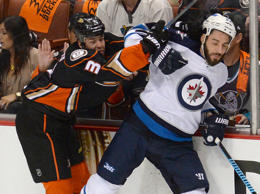Winnipeg Jets right wing Chris Thorburn (22) and Anaheim Ducks defenseman Clayton Stoner (3) battle on the boards in the first period of game two of the first round of the the 2015 Stanley Cup Playoffs at Honda Center.