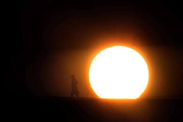 As the sun rises, a man walks across the Santa Fe Dam during a heat wave on March 26, in Irwindale, Calif.  Irfan Khan/Los Angeles Times via Getty Images
