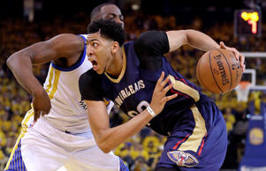 New Orleans Pelicans' Anthony Davis drives past Golden State Warriors' Draymond Green during the second half in Game 1 of the NBA basketball playoffs on April 18, 2015, in Oakland, Calif.