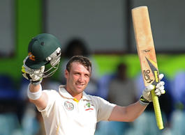 File: Australian batsman Phillip Hughes raises his bat and helmet in celebration after scoring a century (100 runs) during the fourth day of the third and final Test match between Australia and Sri Lanka at The Sinhalese Sports Club (SSC) Ground in Colombo on September 19, 2011.