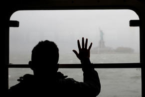 NEW YORK, NY - APRIL 20: A man looks out at the Statue of Liberty in the rain and fog from the Staten Island Ferry on April 20, 2015 in New York City. Much of the East Coast experienced heavy rains and high winds following a beautiful spring weekend. (Photo by Spencer Platt/Getty Images)