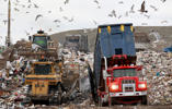 File -- In this Wednesday, Dec. 14, 2011 file photo a garbage truck, right, empties its load as bulldozers process the waste at the Central Landfill, in Johnston, R.I. The landfill has been operating without a federally required permit for 16 years, according to the Conservation Law Foundation, a top New England environmental group, which has sent a notification indicating it plans to sue under the Clean Air Act. (AP Photo/Steven Senne, File) Attribution: Steven Senne/AP
