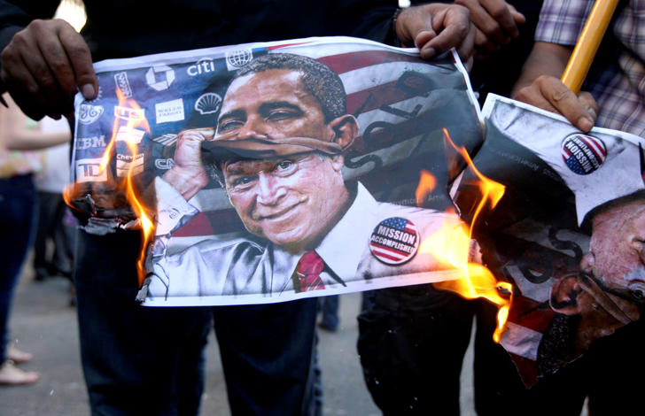 Activists burn a poster of Bush disguised as Obama during a protest in Awkar, Lebanon.
