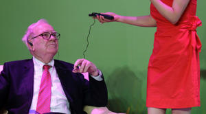 A woman helps billionaire financier and Berkshire Hathaway Chief Executive Warren Buffett test a translator device.