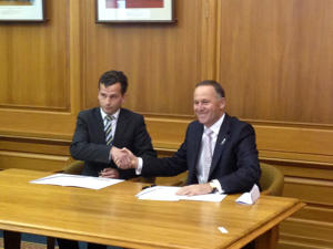 File photo: New Zealand Prime Minister John Key (R) signs a confidence and supply agreement with ACT MP David Seymour in Wellington on Sept. 29, 2014.