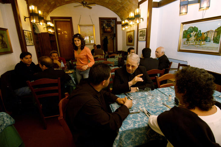 Customers including clergymen wait for their meal at 'Ristorante da Roberto's al Passetto di Borgo' in Borgo Pio, the area near the Vatican in Rome, Italy, April 23, 2005.