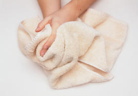 Person drying their hands on a cream towel
