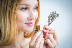Woman smelling a bottle of thyme essential oil to calm her mind.