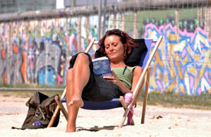 A woman, name not given, enjoys the sun and reading in her book as she relaxes in a beach chair in a beach bar next to the East Side Gallery, in background, in Berlin on Monday, April 27, 2009. (AP Photo/Gero Breloer)
