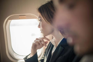 Passenger looking out of airplane window. Cultura/Getty Images