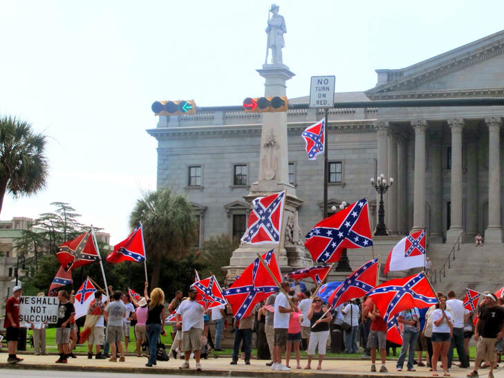 Supporters of keeping the Confederate battle flag flying at a Confederate monument at the South Carolina Statehouse wave flags during a rally in front of the statehouse in Columbia, S.C., on Saturday, June 27, 2015.