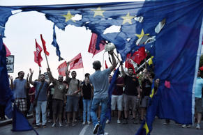 Members of left wing parties shout slogans behind a burning European Union flag during an anti-EU protest in the northern Greek port city of Thessaloniki, Sunday, June 28, 2015. Greek Prime Minister Alexis Tsipras says the Bank of Greece has recommended that banks remain closed and restrictions be imposed on transactions, after the European Central Bank didn't increase the amount of emergency liquidity the lenders can access from the central bank. (AP Photo/Giannis Papanikos)