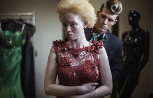 South African lawyer and part-time fashion model Thando Hopa (L), an albino, tries on an evening dress by South African fashion designer Gert-Johan Coetzee (R) during a mock-up fitting session at his workshop on June 13, 2015 in Johannesburg.