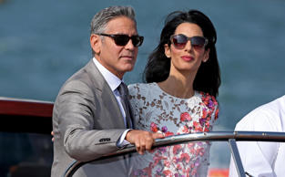 epa04421756 Newlywed couple, US actor George Clooney (L) and his wife Amal Alamuddin (R) stand on a taxi boat, in Venice, Italy, 28 September 2014. Clooney and Alamuddin got married the day before at the Aman Resort hotel. EPA/ALESSANDRO DI MEO