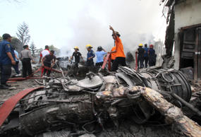 Firefighters and military personnel work at the site where an Air Force cargo plane crashed in Medan, North Sumatra, Indonesia, Tuesday, June 30, 2015. An Indonesian Air Force Hercules C-130 plane with 12 crew aboard has crashed into a residential neighborhood in the country's third-largest city Medan.