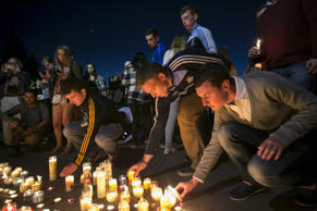 People place candles in front of a memorial during a candlelight vigil for the victims of the Berkeley balcony collapse in Berkeley, California, June 17, 2015.