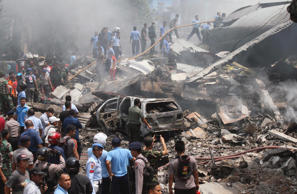 Firefighters and military personnel inspect the site where an Air Force cargo plane crashed in Medan, North Sumatra, Indonesia, tuesday, June 30, 2015. An Indonesian Air Force Hercules C-130 plane with 12 crew aboard has crashed into a residential neighborhood in the country's third-largest city Medan.
