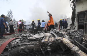 Firefighters and military personnel work at the site where an Air Force cargo plane crashed in Medan, North Sumatra, Indonesia.