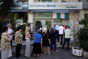 People stand in a queue to use an ATM outside a closed bank, next to a sign on the plant, bottom right, reading ''NO'' in Athens, Tuesday, June 30, 2015. It's crunch time for Greece, with the European part of its international bailout expiring Tuesday and with it any possible access to the remaining rescue loans it contains that it needs to pay its debts. As a result, the government is unlikely to repay a roughly 1.6 billion-euro ($1.87 billion) debt to the International Monetary Fund due Tuesday, too — a move that increases fears the country is heading to a messy default and potential exit from the euro currency.
