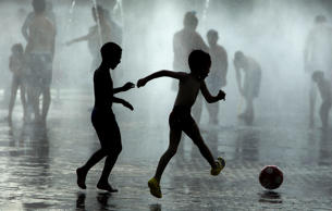 Children play soccer as they cool down in a fountain beside Manzanares river in Madrid on Monday, June 29, 2015. Weather stations across Spain are warning people to take extra precautions as a heat wave engulfs much of the country, increasing the risk of wildfires. The country's meteorological agency says a mass of hot air originating in Africa is moving northwards, bringing with it until at least Monday temperatures reaching 40 Celsius (104 Fahrenheit). Andres Kudacki/AP