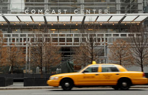 A taxi drives past Comcast Center, home to the headquarters of Comcast Corp., in Philadelphia, Pennsylvania, U.S., on Wednesday, Feb. 18, 2009. Police say a man who took a 300-mile cab ride across Pennsylvania to surprise his fiancee has been jailed because he couldn't pay the $749 fare.