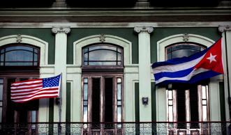 In this Jan. 19, 2015 file photo, a Cuban and American flag wave from the balcony of the Hotel Saratoga in Havana.