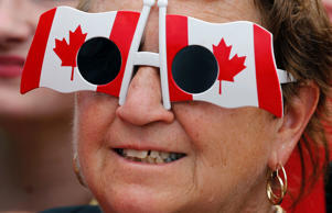 A woman wears sunglasses in the shape of Canadian flags during Canada Day celebrations on Parliament Hill in Ottawa July 1, 2014.