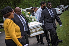 Pallbearers carry the casket of 3-year-old Ji'Aire Lee at Resurrection Cemetery in Clinton, Maryland June 5, 2015.