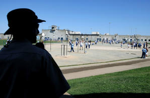 A 2007 file photo shows a prison officer watching inmates, at the Mule Creek State Prison, as they exercise in the yard.