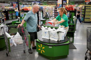 A customer speaks to the cashier as he checks out at a Walmart Neighborhood Market in Bentonville, Arkansas.