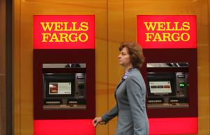 A woman walks past teller machines at a Wells Fargo bank in San Francisco, California.