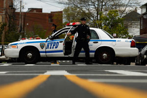 File photograph of an NYPD police officer standing outside of his vehicle in New York City.