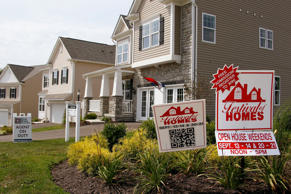 In this photo made on Wednesday, Sept. 10, 2014, signs welcome visitors to a model home as construction is under way at a housing development in Zelienople, Pa.