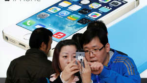 A staff of a China Mobile shop (R) explains a function of the iPhone 5s to a customer in Beijing January 17, 2014.