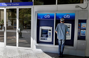 A man uses a CitiBank ATM Monday, July 14, 2014, in Oakland, Calif. Citigroup said Monday that its net income dropped in the second quarter after it took a $3.8 billion charge to settle claims over its risky subprime mortgage business.