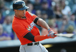 Miami Marlins' Giancarlo Stanton follows the flight of his RBI-single against the Colorado Rockies in the seventh inning of the Rockies' 7-4 victory in a baseball game in Denver on Sunday, Aug. 24, 2014.