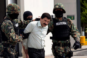 "Drug trafficker Joaquin ""El Chapo"" Guzman is escorted to a helicopter by Mexican security forces on Feb. 22 at Mexico's International Airport in Mexico City. Mexico's apprehension of the world's most-wanted drug boss struck a blow to a cartel that local and U.S. authorities say swelled into a multinational empire, fueling killings around the world."