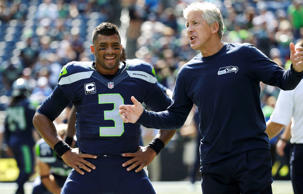 Seattle Seahawks coach Pete Carroll, right, talks with quarterback Russell Wilson before the team's NFL football game against the Denver Broncos, Sunday, Sept. 21, 2014, in Seattle.