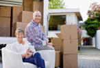 Couple sitting with moving and boxes.